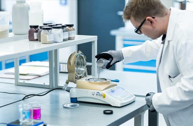 Mitarbeiter mit unterschiedlichen Materialproben im Labor